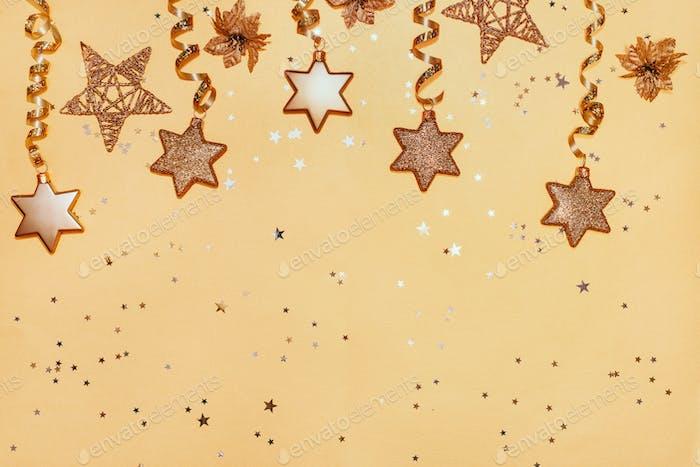 Weihnachtskugeln, Sterne, Geschenkboxen, Bänder und Kerzen Neujahrsdekorationen auf gelbem Hintergrund.