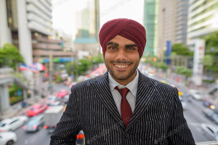 Happy Indian businessman with turban smiling outdoors in city
