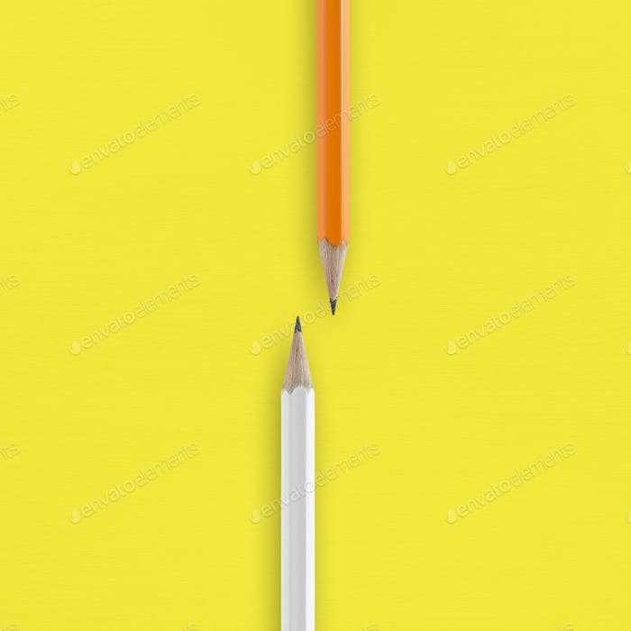 White and orange pencils on yellow background