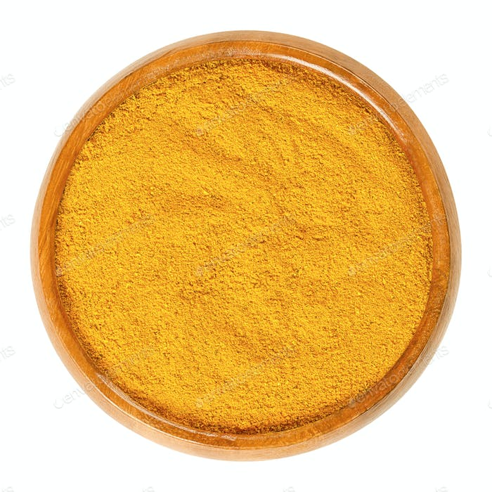 Curry powder in wooden bowl over white