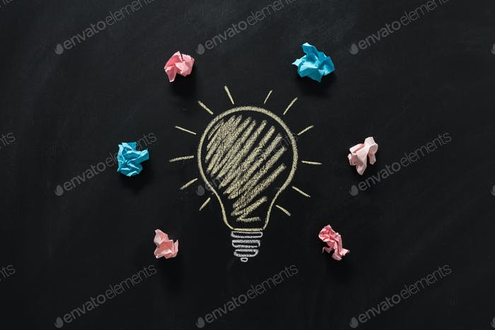 top view of paper rubbish lying around of electric bulb drawn on blackboard