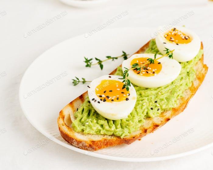 Avocado-Toast mit geröstetem Brot weichgekochte Eier mit Kräutern