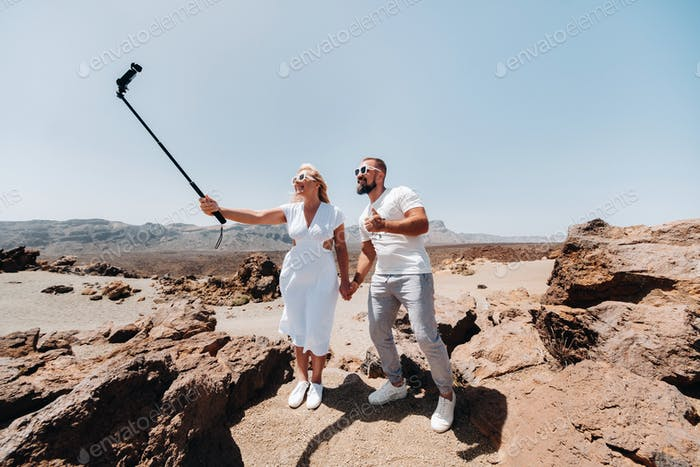a stylish woman takes a selfie in the crater of the Teide volcano. Desert landscape in Tenerife