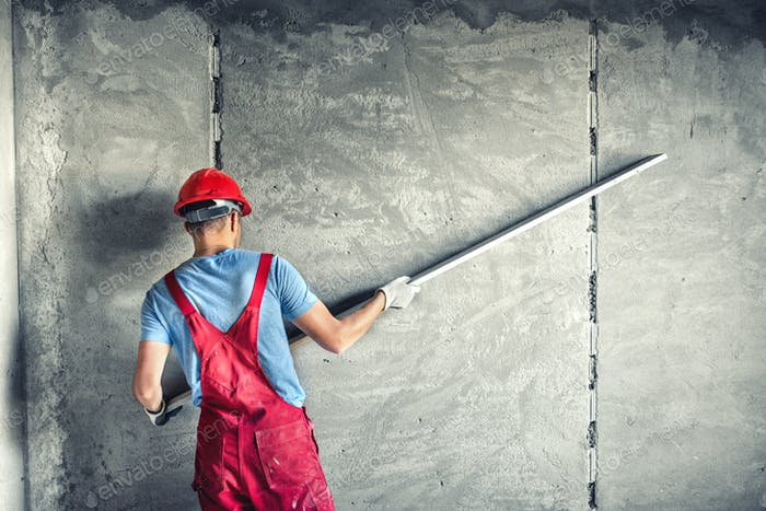 industrial worker with plastering tools renovating a house. builder worker plastering facade