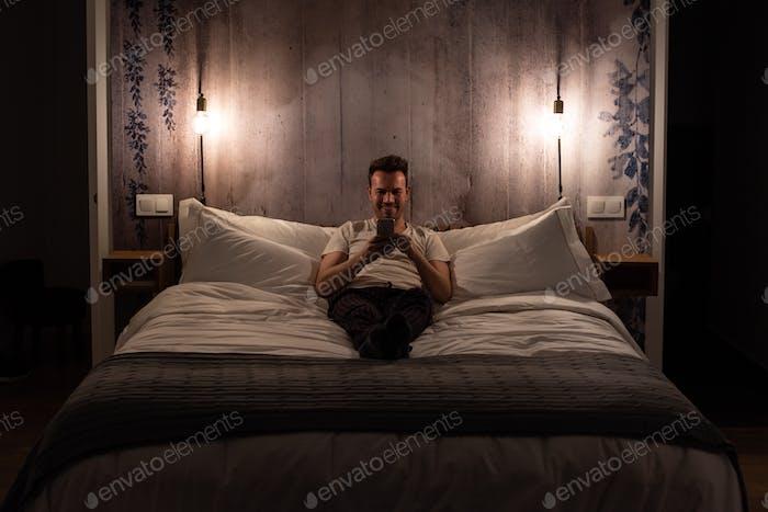 Mann auf dem Handy liegend im Bett