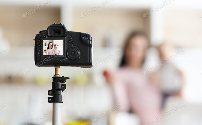 Mother with toddler recording video for webinar, kitchen interior