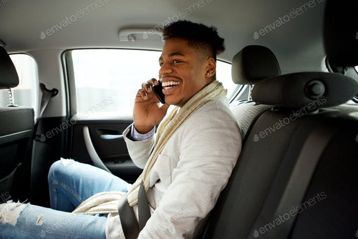 happy young black man sitting in backseat of car and talking with mobile phone