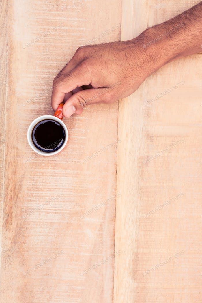 Overhead-Ansicht von Geschäftsmann hält schwarzen Kaffee auf Tisch