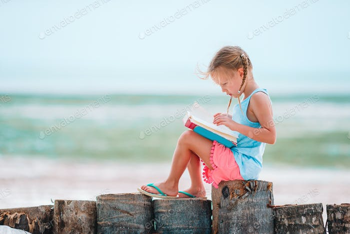 Pequeña niña adorable libro de lectura durante la playa blanca tropical