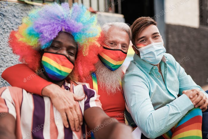 Multiracial gay men at lgbt gay pride event taking a selfie together