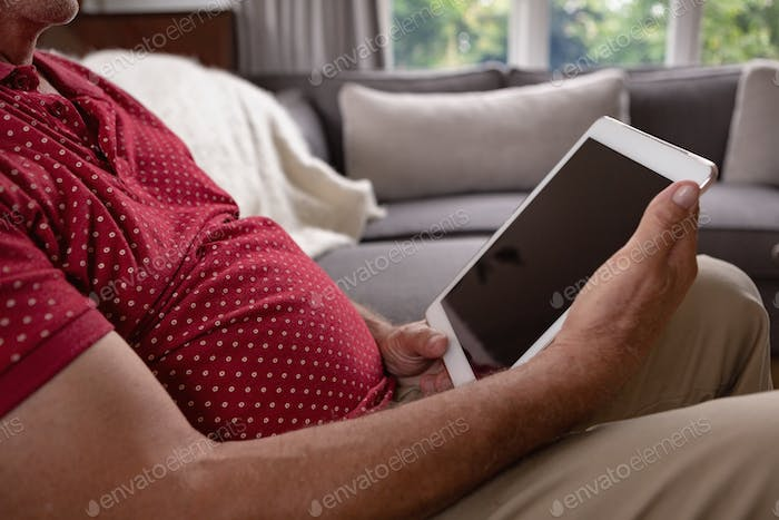 Mid section of active senior Caucasian man using digital tablet on sofa in a comfortable home
