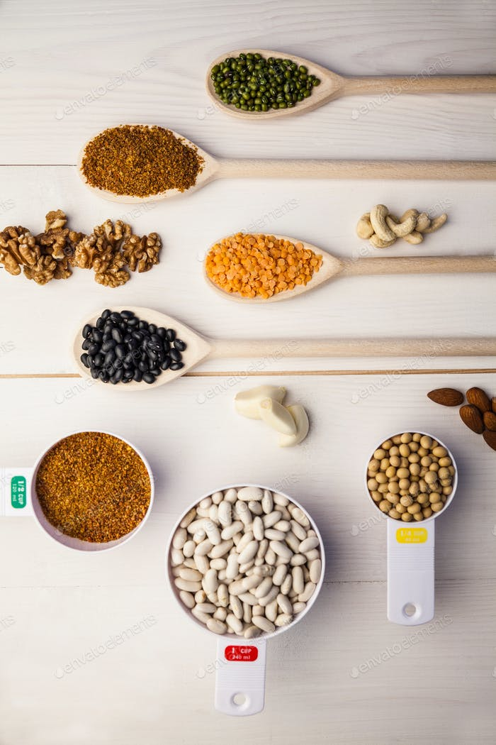 Spoons and cups of pulses and seeds on wooden table