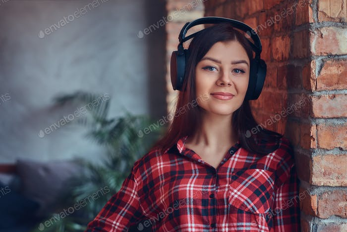 Портрет очаровательной брюнетки в фланелевой рубашке и джинсах lis