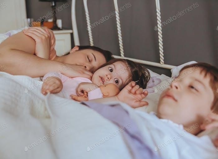 Kleines Mädchen umarmt Puppe über dem Bett liegend