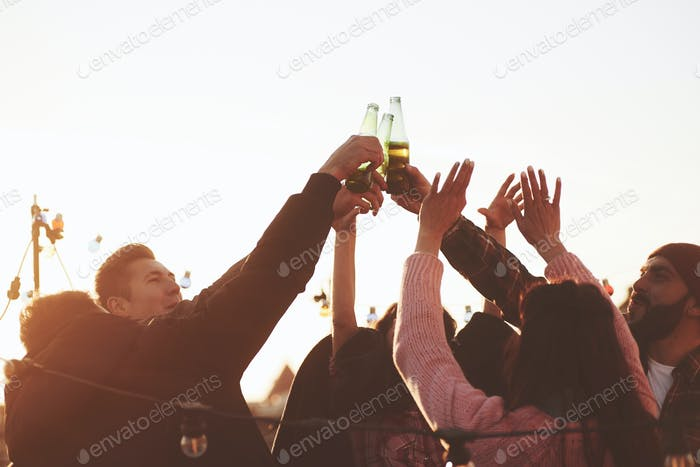 Bottles up. Holidays on the rooftop. Cheerful group of friends raised their hands up with alcohol