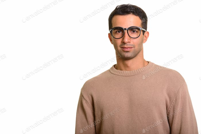 Portrait of young handsome Persian man with nerdy eyeglasses