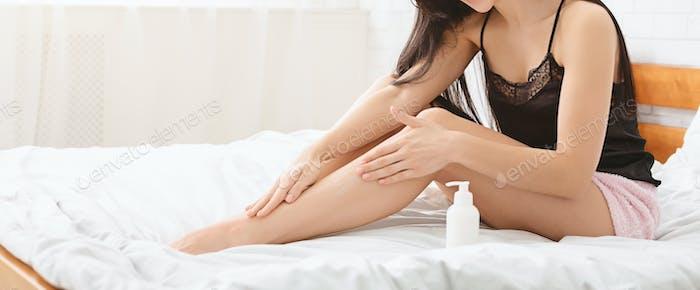 Millennial woman applying moisturizing lotion on legs in bed