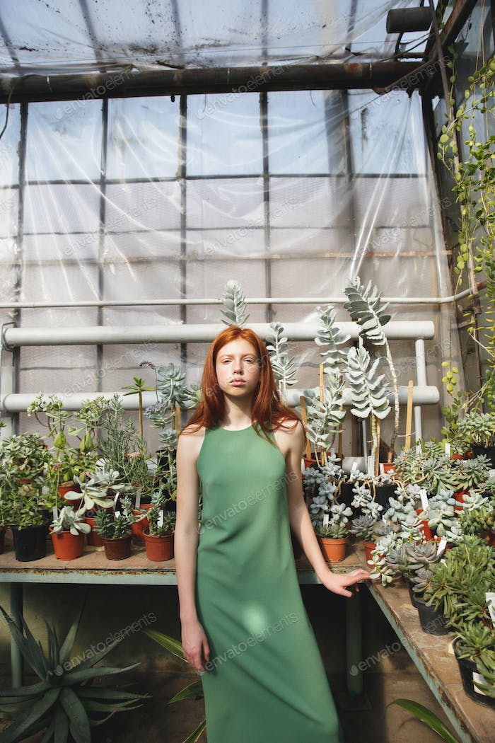 Girl standing in a glass house and looking at camera