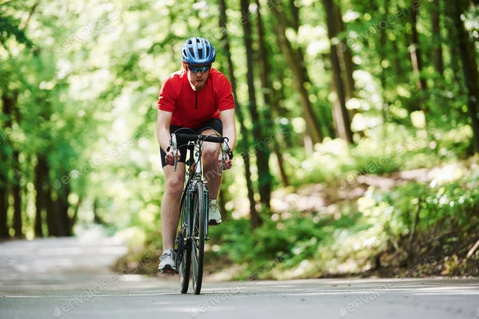 Caucasian ethnicity. Cyclist on a bike is on the asphalt road in the forest at sunny day