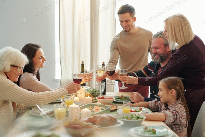 Happy mature and young family members clinking with wine during Christmas toast