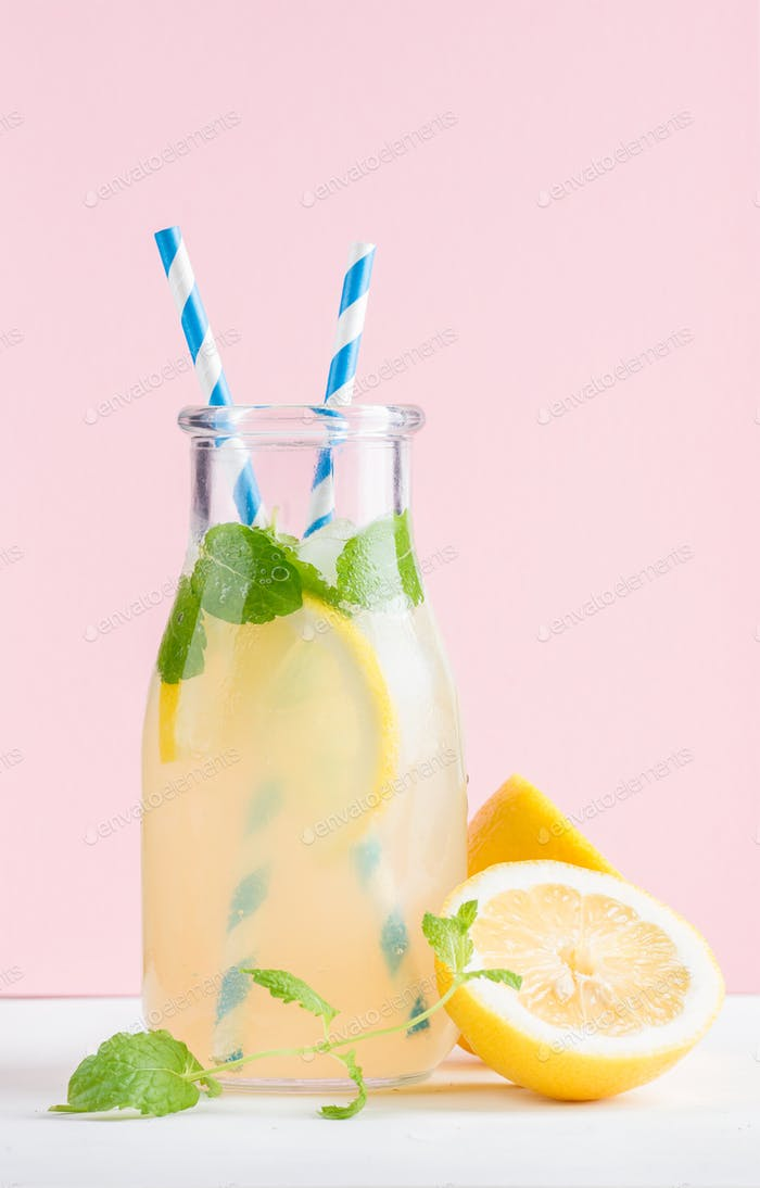 Bottle of homemade lemonade with mint, ice, lemons, paper straws and pastel pink background