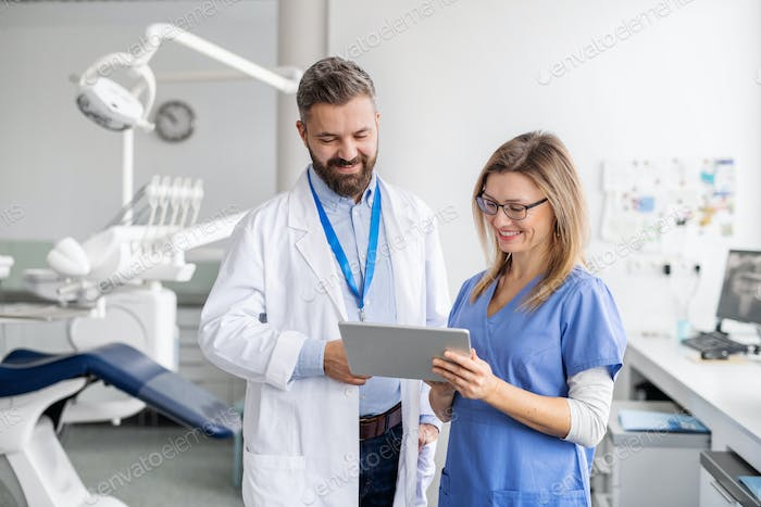A dentist with dental assistant in modern dental surgery, working