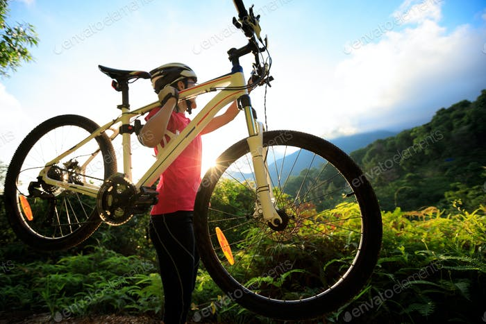 Cyclist with mountain bike in sunrise mountains
