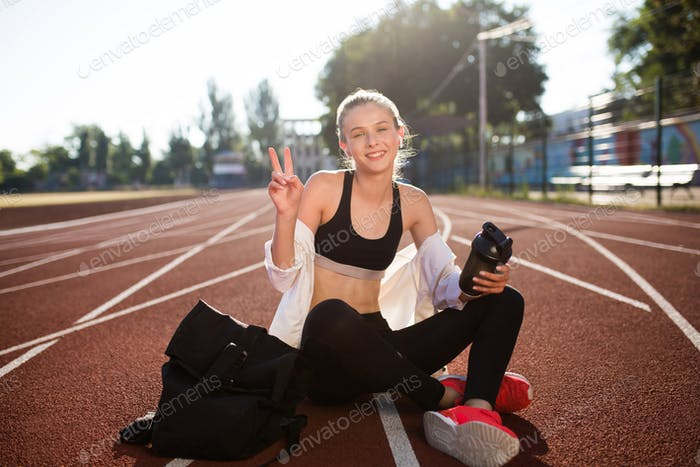 Cheerful girl happily looking in camera showing peace gesture on running track
