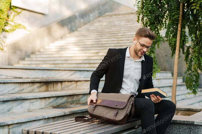Pleased businessman in earphones holding book while sitting on bench