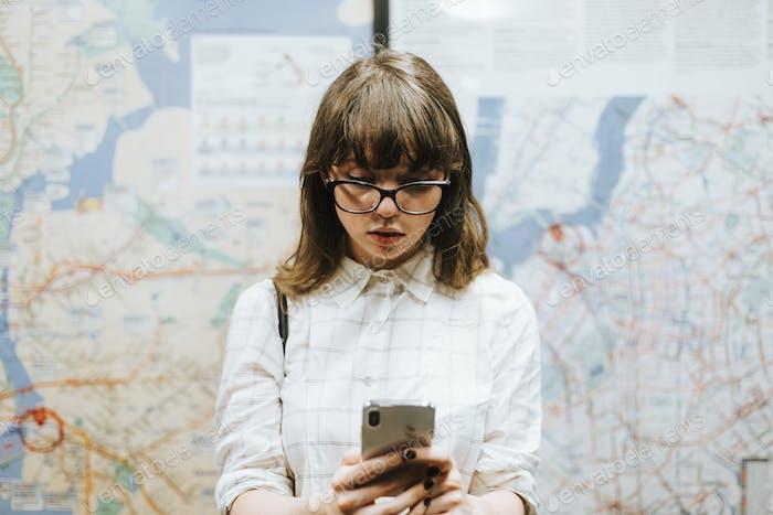 Chica enviando mensajes de texto mientras espera un tren en un andén del metro