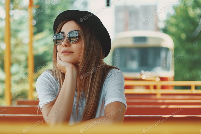 Young woman with hat and sunglasses on a city tour