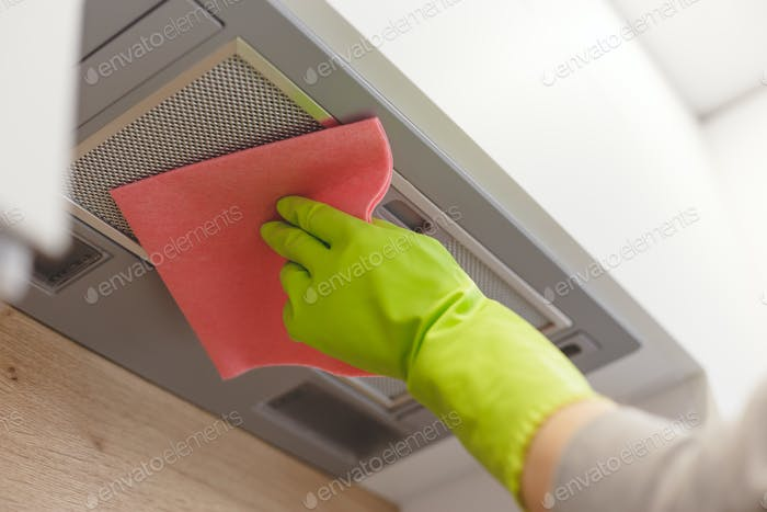 Cleaning domestic cooker hood grid with pink cloth fiber napkin.