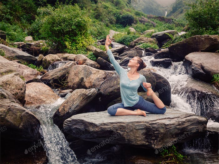 Sorty fit woman doing yoga asana outdoors at tropical waterfall