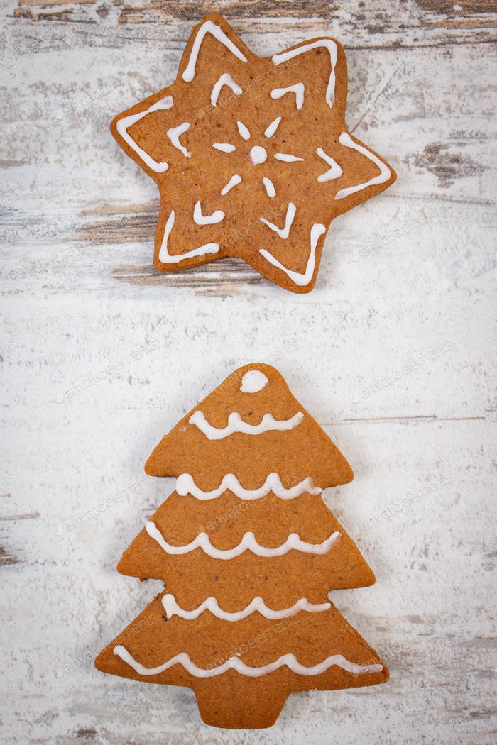 Fresh baked decorated gingerbread on old wooden background, christmas time