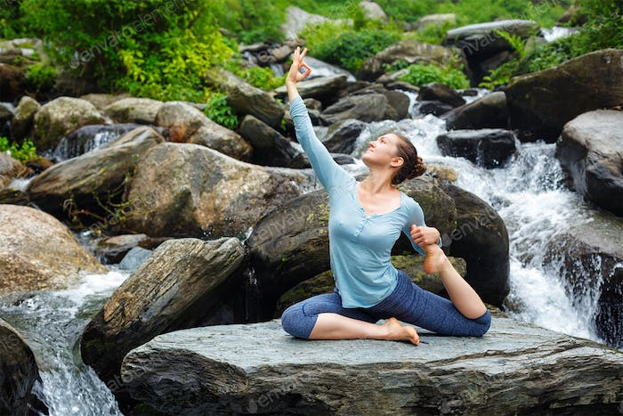 Woman doing yoga outdoors at tropical waterfall