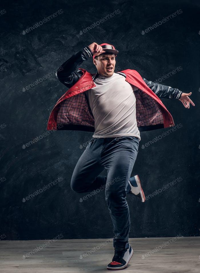 Stylish guy performs breakdance acrobatic elements.