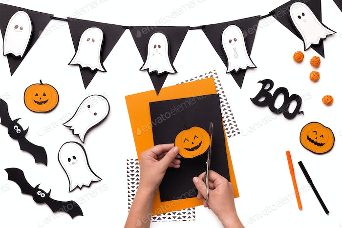 Woman cutting out Halloween smiling pumpkin of paper