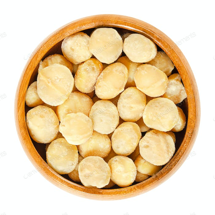 Roasted macadamia nuts in wooden bowl over white