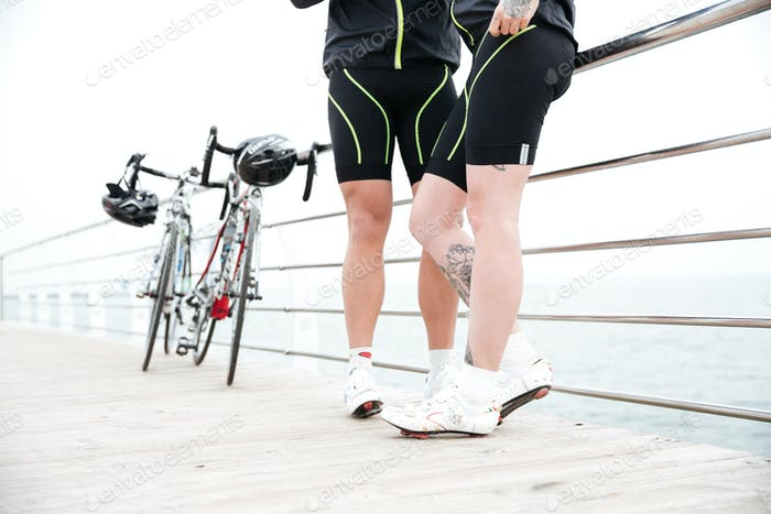 Couple in bike shorts with bicycles standing on pier