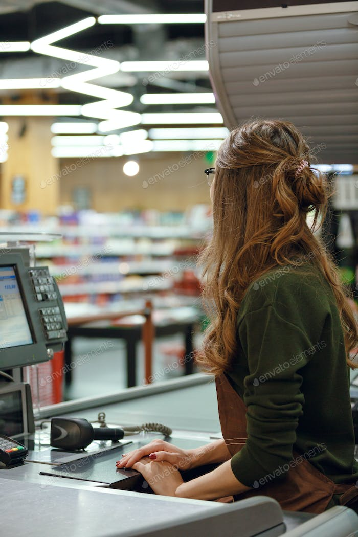 Cashier on workspace in supermarket shop.