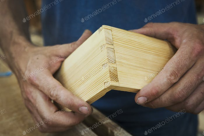 Close up of person working a boat-builder's workshop, joining together two pieces of wood.
