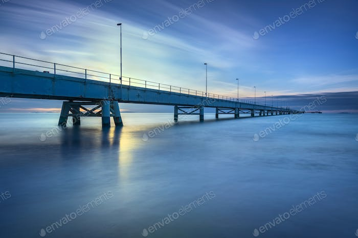 Industrial pier on the sea. Side view. Long exposure photography
