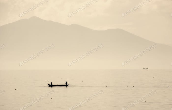 Two people in a small fishing boat on a lake drawing in nets. Mountains in the background.
