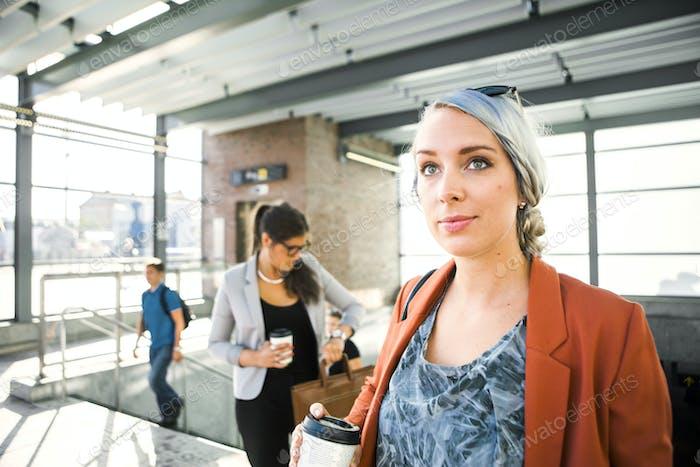 Бизнесвумен, держащий кофейную чашку, стоя на вокзале