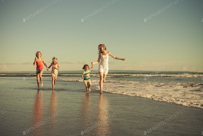 Mother and children running on the beach.
