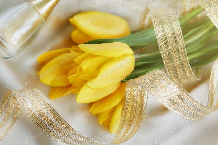 Yellow tulips, perfume and gold ribbon