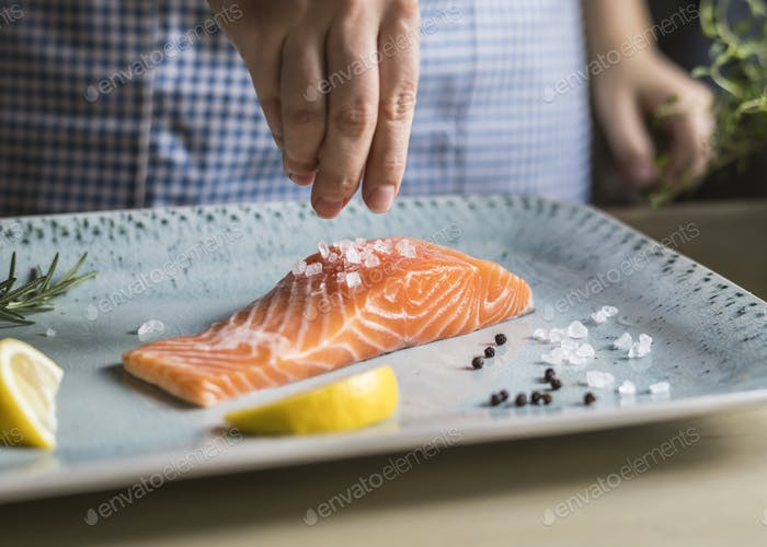 A person seasoning a fillet of salmon food photography recipe idea