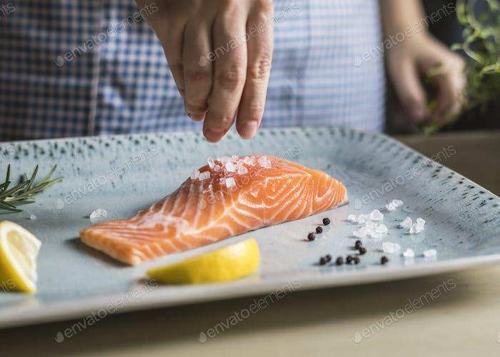 Eine Person Würze ein Filet von Lachs Essen Fotografie Rezept Idee
