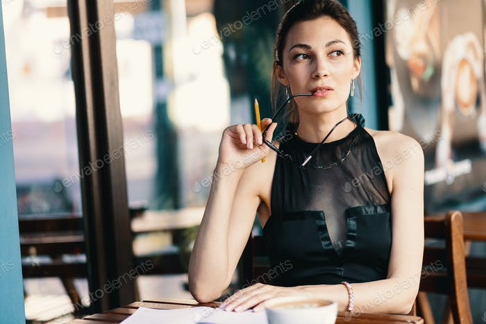 Elegant young woman took off her glasses while taking a break of her agenda