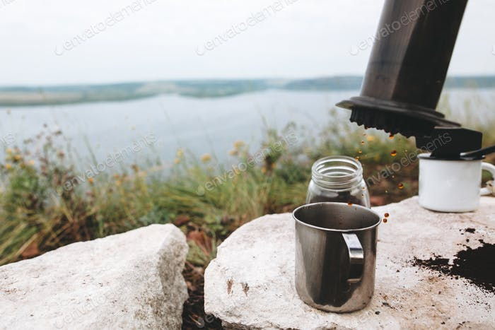 Focus on grass on cliff and blurred image of traveler pressing aeropress